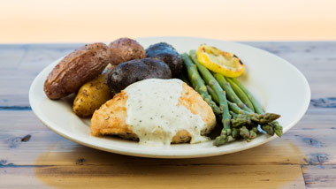 plate of chicken, potatoes and asparagus on a wooden background